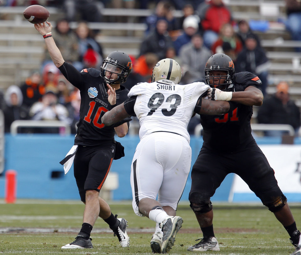 Photo - Oklahoma State's Clint Chelf (10) throws a pass during the Heart of Dallas Bowl football game between the Oklahoma State University (OSU) and Purdue University at the Cotton Bowl in Dallas,  Tuesday,Jan. 1, 2013. Photo by Sarah Phipps, The Oklahoman