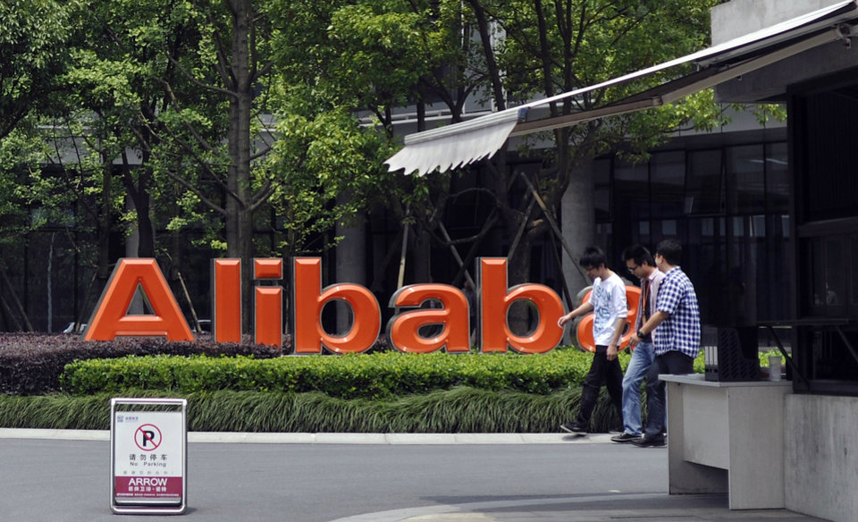 Photo - FILE - In this May 21, 2012 file photo, men walk past the corporate logo at the headquarters compound of Alibaba Group in Hangzhou in eastern China's Zhejiang province. Alibaba Group is aiming to raise $1 billion in a long-awaited IPO likely to have ripple effects across the Internet. The Tuesday, May 6, 2014 filing sets the stage for the technology industry's biggest initial public offering since short messaging service Twitter and its early investors collected $1.8 billion in its stock market debut last fall. (AP Photo/File) CHINA OUT