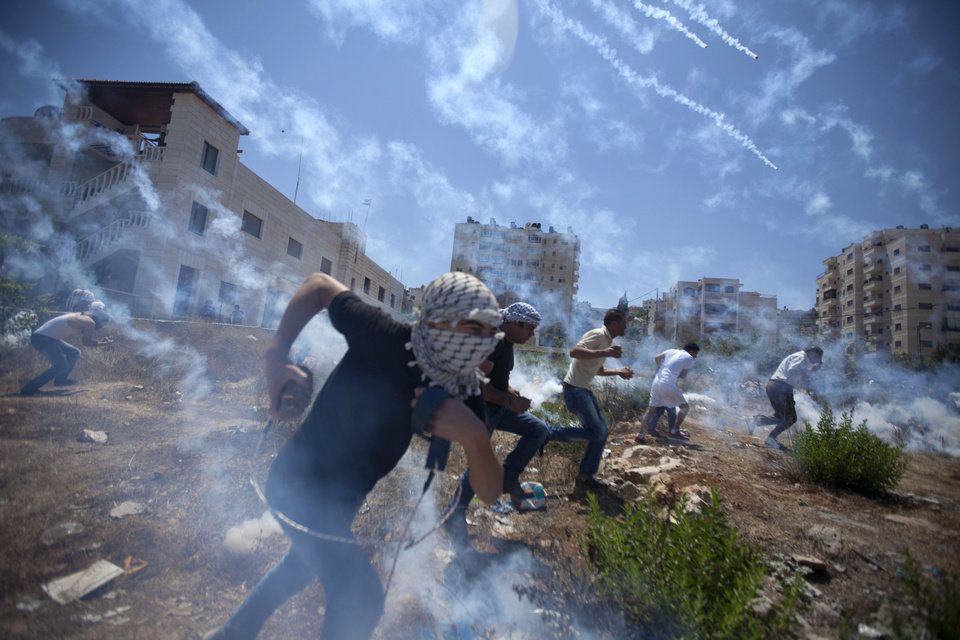 Photo - AP10ThingsToSee - Palestinians run for cover during clashes with Israeli soldiers following a protest against the war in the Gaza Strip, outside Ofer, an Israeli military prison near the West Bank city of Ramallah, Friday, Aug. 1, 2014. (AP Photo/Majdi Mohammed)