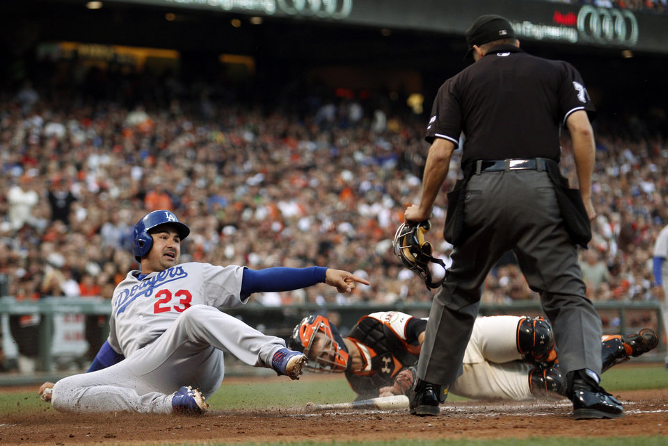 Photo - Los Angeles Dodgers' Adrian Gonzalez (23) pleads with home plate umpire Adam Hamari, right, after being tagged out by San Francisco Giants catcher Buster Posey, center, during the sixth inning of a baseball game on Saturday, July 26, 2014, in San Francisco. (AP Photo/Beck Diefenbach)