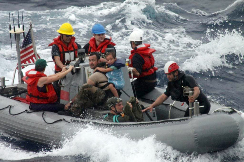 Photo - In this photo provided by the U.S. Coast Guard, sailors from Oliver Hazard Perry-class frigate USS Vandegrift (FFG 49) assist in the rescue of a family with a sick infant via the ship's small boat as part of a joint U.S. Navy, Coast Guard and California Air National Guard rescue effort, Sunday, April 6, 2014. Eric and Charlotte Kaufman said their daughter Lyra's medical condition continued to improve after they boarded the San Diego-bound Vandegrift hundreds of miles off the Mexican coast so the girl could get to a medical facility. (AP Photo/U.S. Coast Guard)