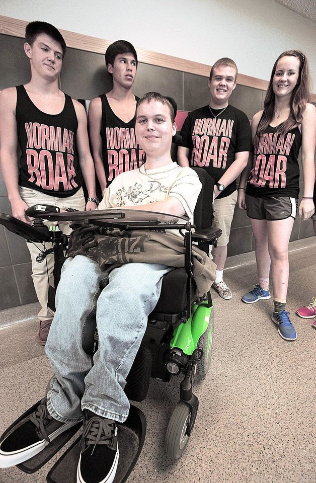 "Norman High School senior Jake Pyle poses with students wearing ""Norman Roar"" T-shirts, which were sold to help fund a music video contest entry that features Pyle. <strong>David McDaniel - The Oklahoman</strong>"
