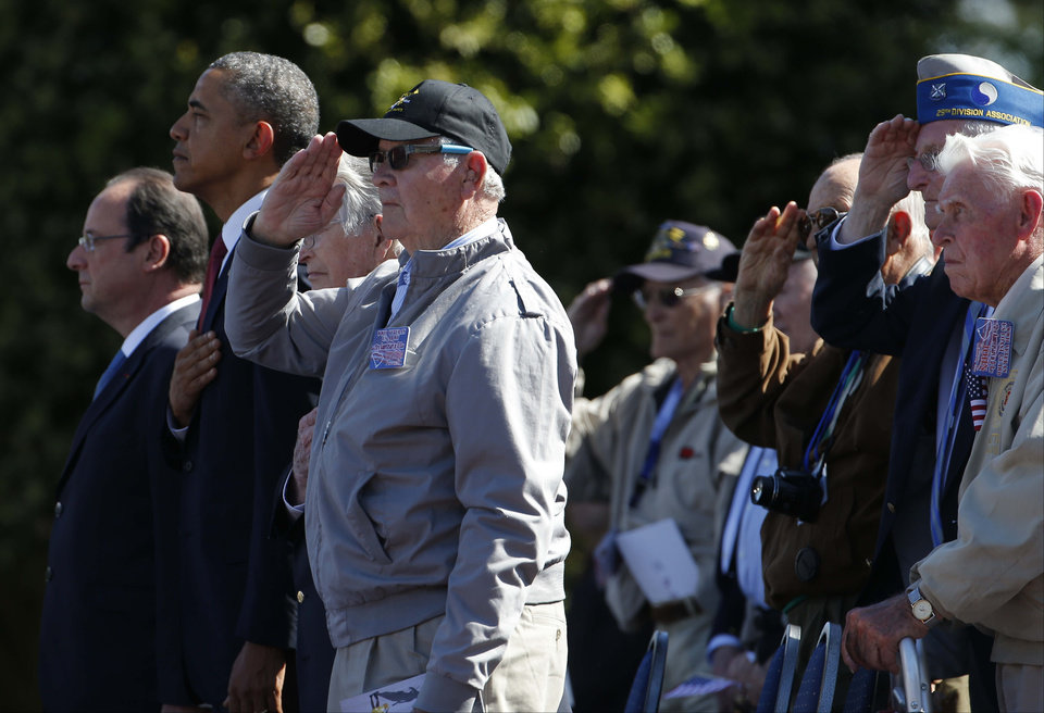 Photo - U.S. President Barack Obama, second left and French President Francois Hollande stand with veterans, at Normandy American Cemetery at Omaha Beach as he participates in the 70th anniversary of D-Day in Colleville sur Mer in Normandy, France, Friday, June 6, 2014. (AP Photo/Charles Dharapak)