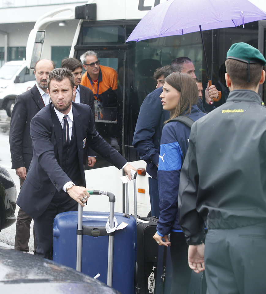 Photo - Italy forward Antonio Cassano, left, carries his luggage upon his arrival with his teammates at Malpensa airport after landing from Brazil, in Milan, Italy, Thursday, June 26, 2014.Pirlo recently quit the national team. Pirlo had said before the tournament he would quit international football after Brazil. Italy was disqualified from the World Cup after loosing to Uruguay in their group stage round.  (AP Photo/Luca Bruno)