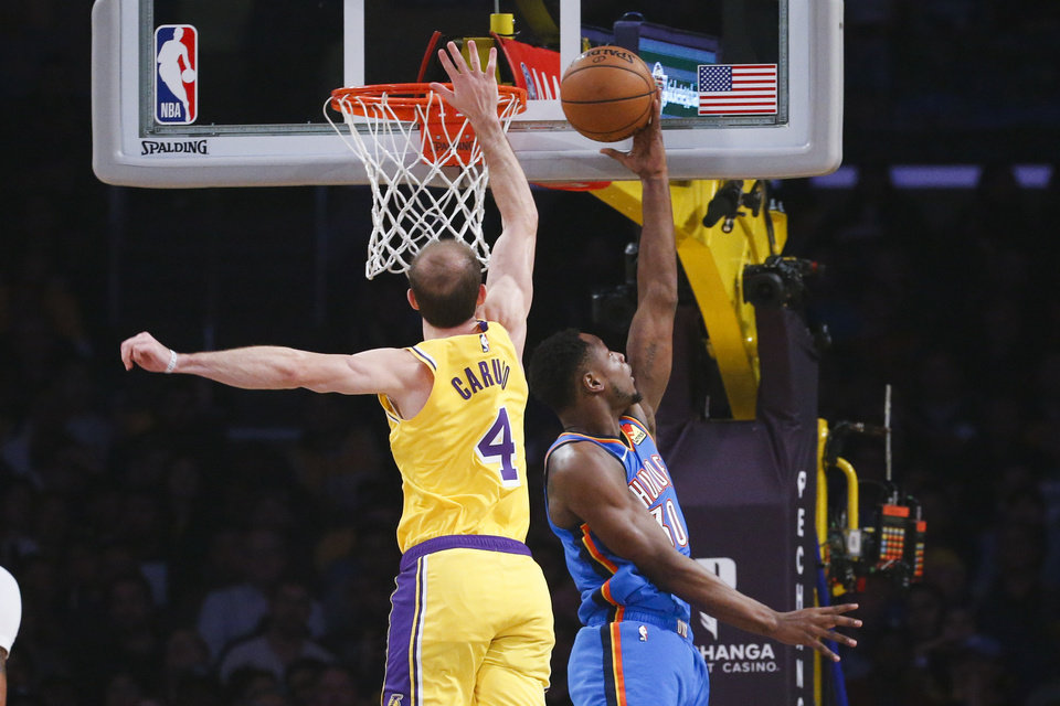 Photo - Oklahoma City Thunder's Deonte Burton (30) goes up for a layup under pressure from Los Angeles Lakers' Alex Caruso (4) during the first half of an NBA basketball game, Tuesday, Nov. 19, 2019, in Los Angeles. (AP Photo/Ringo H.W. Chiu)