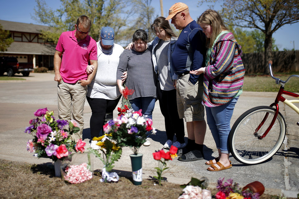 Photo -  Neighbors pray near flowers close to the home of Cecille Short, who was mauled to death by two dogs Thursday in northwest Oklahoma City. [Photo by Bryan Terry, The Oklahoman]