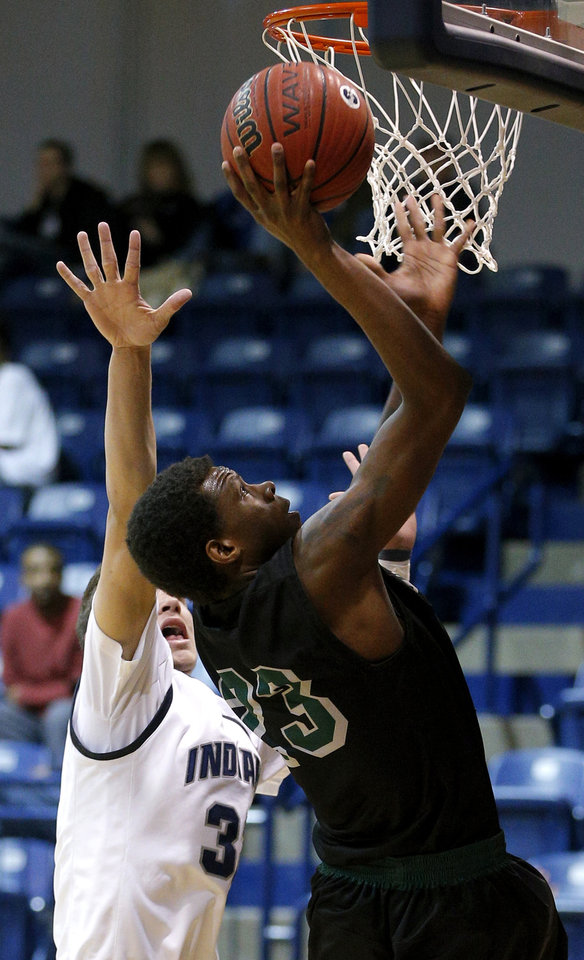 Photo - Norman North's Ronnie Thompson goes to the basket past El Reno's Kade Hileman.   Photo by Bryan Terry, The Oklahoman