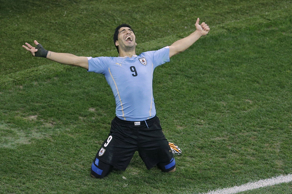 Photo - FILE - In this  June 19, 2014 file photo, Uruguay's Luis Suarez celebrates scoring 2-1 during the group D World Cup soccer match between Uruguay and England at the Itaquerao Stadium in Sao Paulo, Brazil. Barcelona reached agreement with Liverpool on the transfer of Luis Suarez on Friday July 11, 2014, giving the troubled striker a chance to rehabilitate his image when his latest biting ban is over. Suarez will travel to Barcelona next week for a medical and to sign a five-year contract. (AP Photo/Michael Sohn, File)