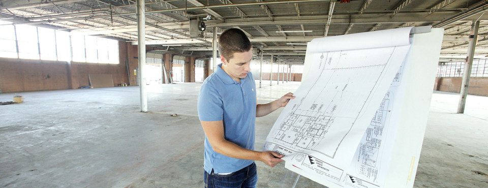 Photo - Keith Winter goes over architectural plans for the renovation a warehouse at 425 E Hill St., the future home of HomeWetBar.com.  PAUL B. SOUTHERLAND - The Oklahoman