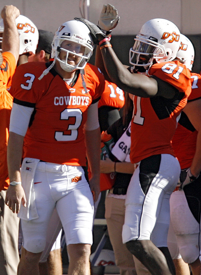 Oklahoma State's Justin Blackmon (81) celebrates with Brandon Weeden (3) as he comes off the field late in the fourth quarter during the college football game between the Oklahoma State University Cowboys (OSU) and the Baylor University Bears at Boone Pickens Stadium in Stillwater, Okla., Saturday, Nov. 6, 2010. Weeden set an OSU single game passing record.Photo by Chris Landsberger, The Oklahoman