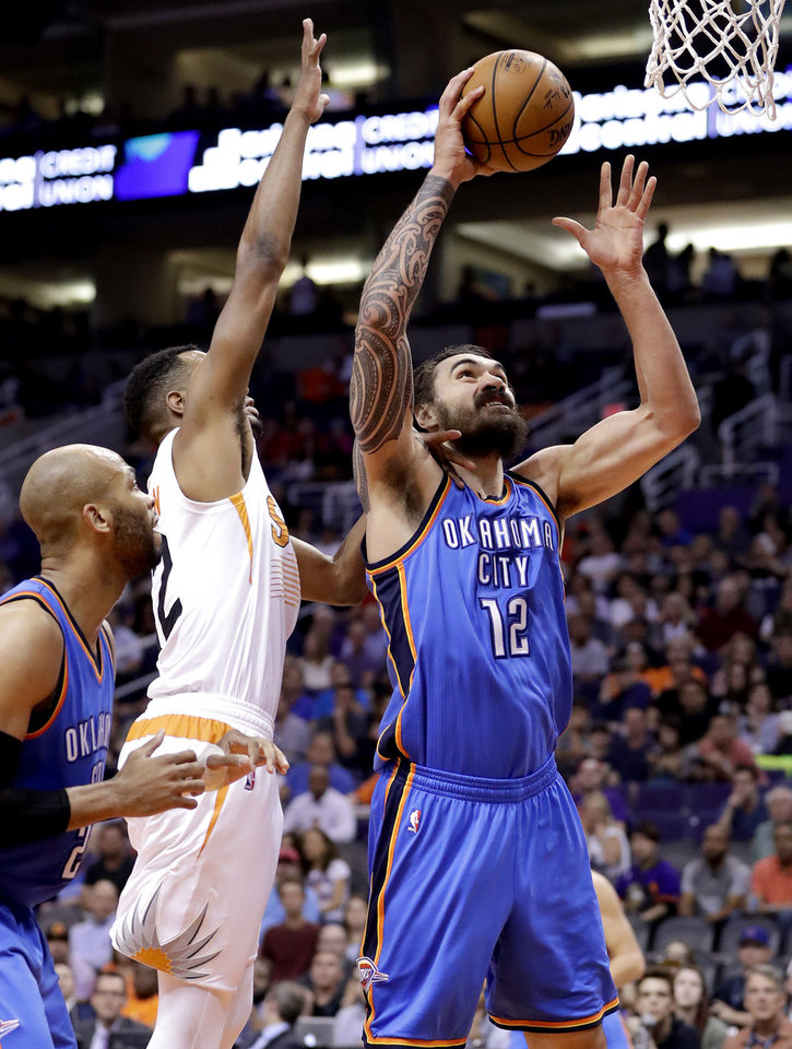 Photo - Oklahoma City Thunder center Steven Adams (12) shoots over Phoenix Suns forward TJ Warren (12) during the first half of an NBA basketball game, Friday, April 7, 2017, in Phoenix. (AP Photo/Matt York)