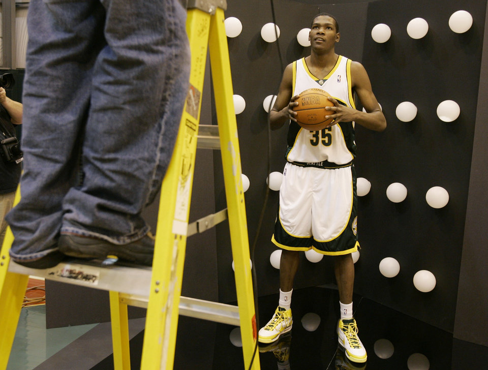 Photo - Seattle SuperSonics' Kevin Durant looks up to a photographer on a ladder as he poses for photos during the NBA basketball team's annual media day Monday, Oct. 1, 2007, in Seattle. (AP Photo/Ted S. Warren) ORG XMIT: WATW105