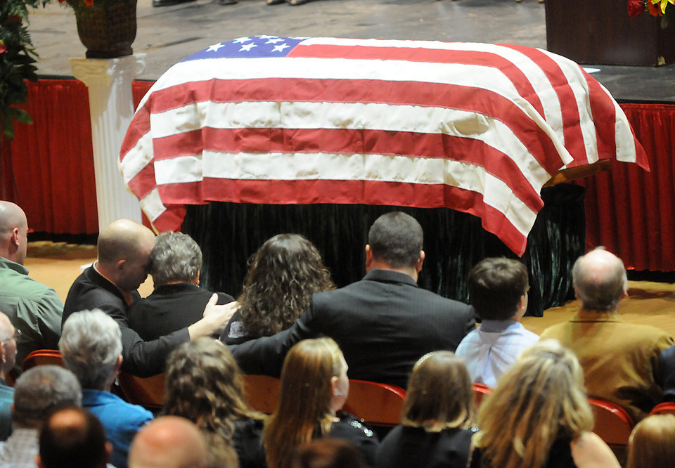 "Family members embrace during the funeral service of Charles ""Chuck"" Poland in Ozark, Ala., Sunday, Feb. 3, 2013. Authorities say Jim Lee Dykes, 65 — a decorated veteran of the Vietnam War known as Jimmy to neighbors — gunned down Poland, a school bus driver, and then abducted a 5-year-old boy from the bus, taking him to an underground bunker on his rural property. (AP Photo/Dothan Eagle, Danny Tindell)"