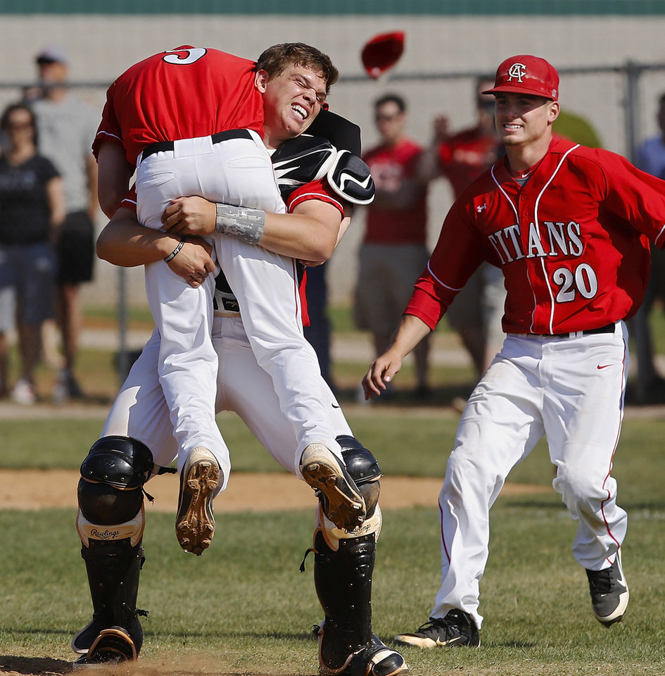 Photo - Carl Albert catcher Cory Zangari  runs to the pitcher mound and hoists pitcher Justin McGregor over his shoulder in a moment of ecstatic celebration after the Titans defeated Claremore to win the   Class 5A high school  state championship game at Edmond Santa Fe High School  Saturday afternoon,  May 11, 2013. Running to join the celebration is senior Garrett Asher. Photo  by Jim Beckel, The Oklahoman.