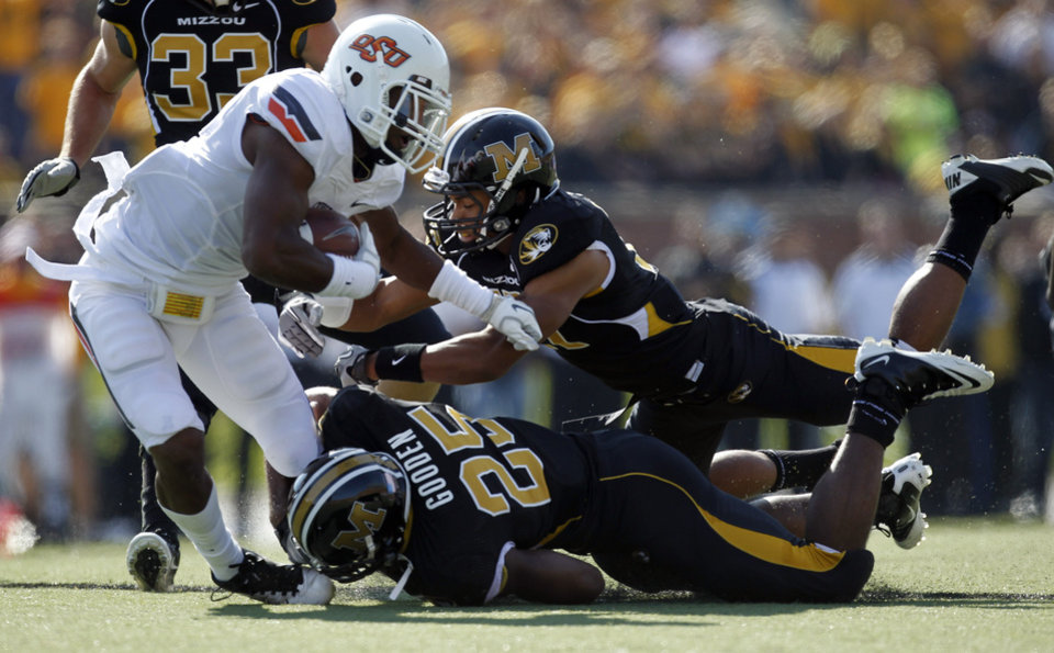 Photo - Oklahoma State running back Joseph Randle, left, runs for an 18-yard gain as Missouri's Matt White and Zaviar Gooden (25) defend during the first half of an NCAA college football game Saturday, Oct. 22, 2011, in Columbia, Mo. (AP Photo/Jeff Roberson)