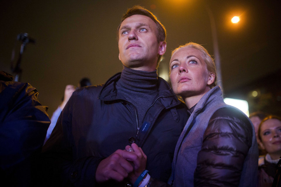 Photo - Russian opposition leader Alexei Navalny with his wife Yulia after his last rally in rain-soaked Moscow, Russia, Friday, Sept. 6, 2013. The anti-corruption blogger and a leader of the Russian protest movement, Navalny will face the incumbent Mayor Sergei Sobyanin, in the upcoming Moscow's mayoral election on Sept. 8. (AP Photo/Evgeny Feldman)
