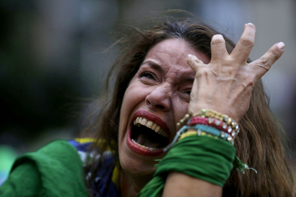 Photo - A Brazil soccer fan cries as Germany scores against her team at a semifinal World Cup match as she watches the game on a live telecast in Belo Horizonte, Brazil, Tuesday, July 8, 2014. (AP Photo/Bruno Magalhaes)
