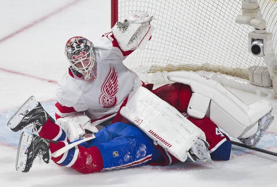 Photo - Detroit Red Wings goaltender Jonas Gustavsson falls on Montreal Canadiens' Michael Bournival during the second period of an NHL hockey game in Montreal, Saturday, April 5, 2014. (AP Photo/The Canadian Press, Graham Hughes)