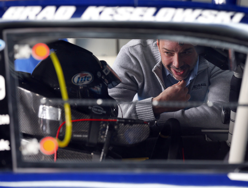 Chad Knaus, crew chief for driver Jimmie Johnson, right, talks with Brad Keselowski, left, during testing for the NASCAR Sprint Cup auto racing series at Charlotte Motor Speedway in Concord, N.C., Tuesday, Dec. 11, 2012. (AP Photo/Chuck Burton)