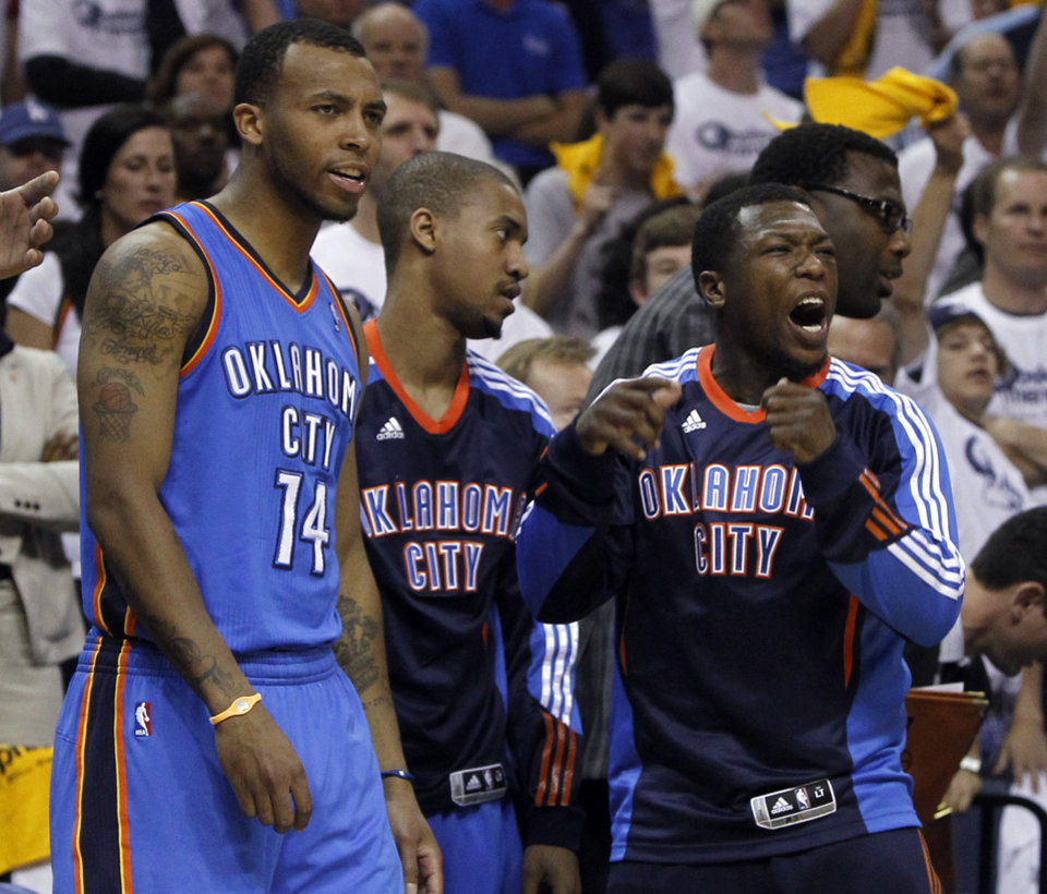 Photo - Oklahoma City Thunder guard Nate Robinson, right, celebrates in the final moments of the third overtime of Game 4 against the Memphis Grizzlies in a second-round NBA basketball playoff series on Tuesday, May 10, 2011, in Memphis, Tenn. Oklahoma City won 133-123 in triple overtime. With Robinson are Daequan Cook (14) and Eric Maynor, center. (AP Photo/Lance Murphey)