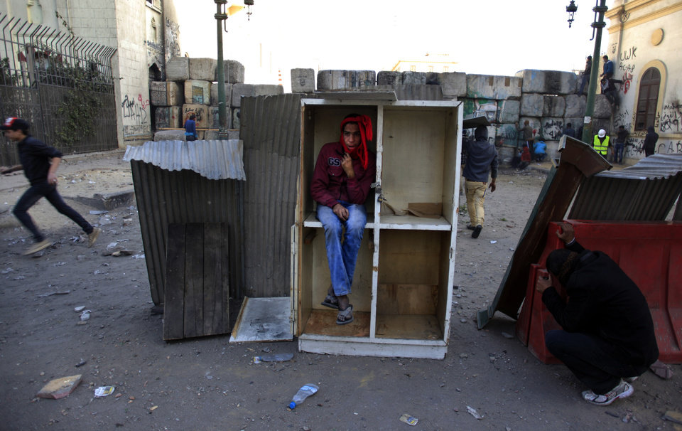Egyptian protesters hide for cover during clashes with riot police, not seen, near Tahrir Square, Cairo, Egypt, Friday, Jan. 25, 2013. Youth activists and opposition groups have called for large rallies to mark the second anniversary of Egypt's Jan. 25, 2011 uprising that toppled long-time authoritarian leader President Hosni Mubarak. (AP Photo/Khalil Hamra) ORG XMIT: KH122