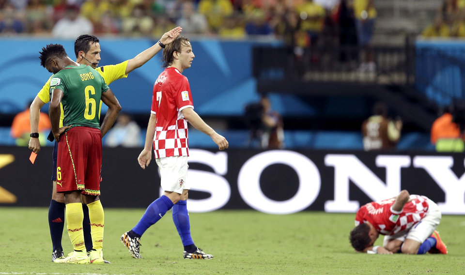 Photo - Referee Pedro Proenca from Portugal gestures after giving a red card to Cameroon's Alex Song (6) as Croatia's Ivan Rakitic looks on during the group A World Cup soccer match between Cameroon and Croatia at the Arena da Amazonia in Manaus, Brazil, Wednesday, June 18, 2014.  (AP Photo/Themba Hadebe)