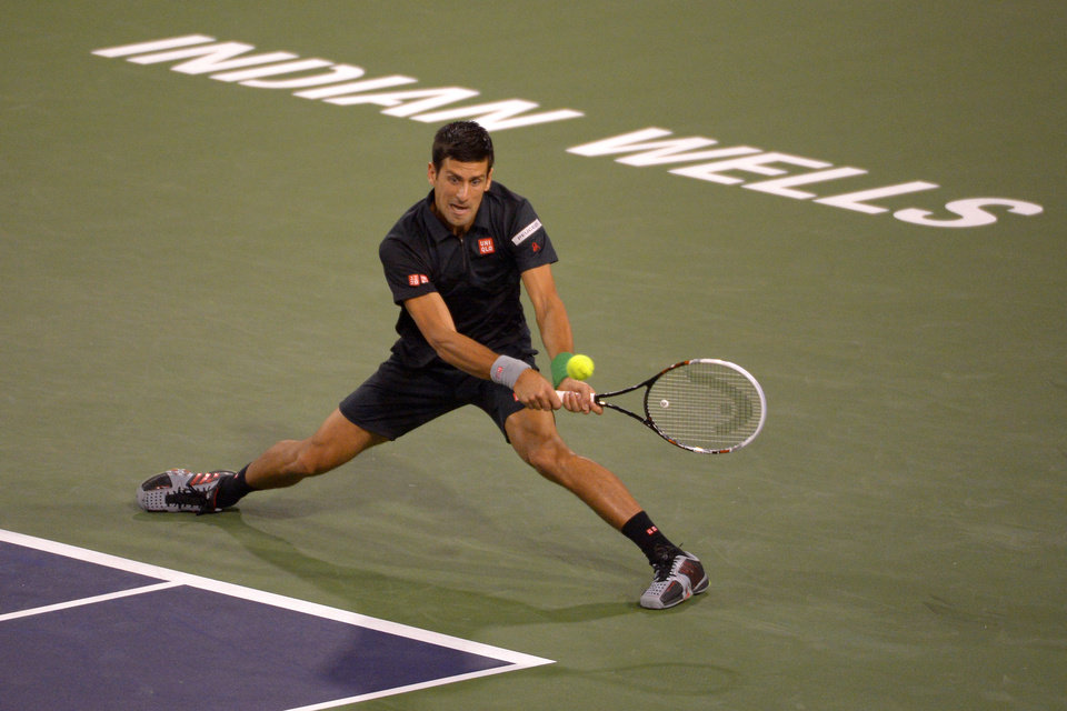 Photo - Novak Djokovic, of Serbia, returns a shot to Victor Hanescu, of Romania, during their match at the BNP Paribas Open tennis tournament, Sunday, March 9, 2014, in Indian Wells, Calif. (AP Photo/Mark J. Terrill)