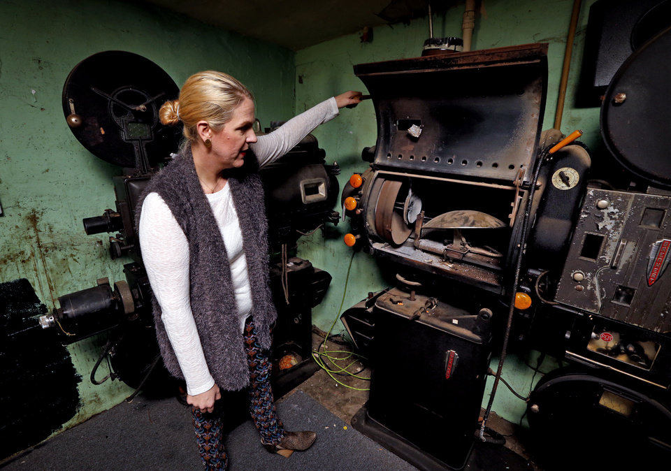 Photo -  Aimee Ahpeatone examines the projectors discovered inside the Yale Theater on Thursday. [Photo by Steve Sisney, The Oklahoman]