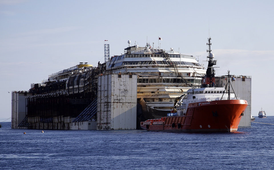 Photo - The Costa Concordia cruise wreck is maneuvered into position to be towed away from the tiny Tuscan island of Isola del Giglio, Italy, Wednesday, July 23, 2014.  After more than two years since it slammed into a reef along the coastline of Isola del Giglio the wreck has begun its last journey, to the Italian port of Genoa, where it will be scrapped. 32 people died in the incident. (AP Photo/Gregorio Borgia)