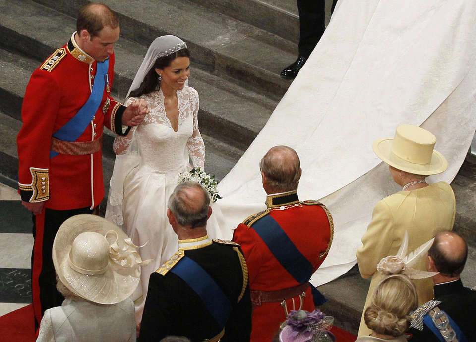 Photo - Britain's Prince William, back left, and his wife Kate, the Duchess of Cambridge, second from left in back, greet Britain's Queen Elizabeth II, right, as Britain's Prince Philip, third from left in front, Britain's Prince Charles, second from left in front, and Camilla, Duchess of Cornwall, front left, look on,  during their wedding at Westminster Abbey in London, Friday, April 29, 2011. (AP Photo/Kirsty Wigglesworth, Pool)