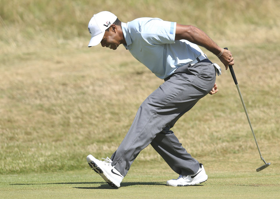 Photo - Tiger Woods of the United States reacts after putting on the 9th green during the second round of the British Open Golf Championship at Muirfield, Scotland, Friday July 19, 2013. (AP Photo/Scott Heppell)