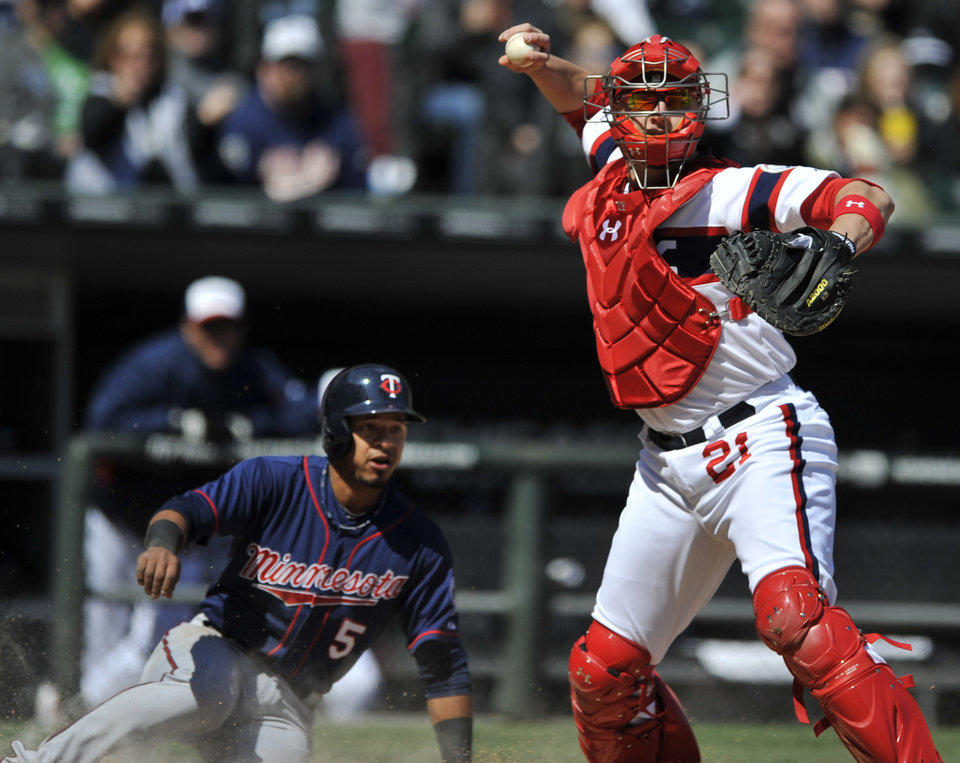 Photo - Chicago White Sox catcher Tyler Flowers, right, looks to throw to first base after forcing out Minnesota Twins' Eduardo Escobar at home plate during the seventh inning of a baseball game in Chicago, April 21, 2013. Minnesota won 5-3. (AP Photo/Paul Beaty)