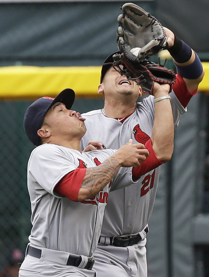 Photo - St. Louis Cardinals first baseman Allen Craig (21) catches a fly ball hit by Cincinnati Reds' Zack Cozart as he collides with second baseman Kolten Wong in the first inning of a baseball game on Thursday, April 3, 2014, in Cincinnati. (AP Photo/Al Behrman)