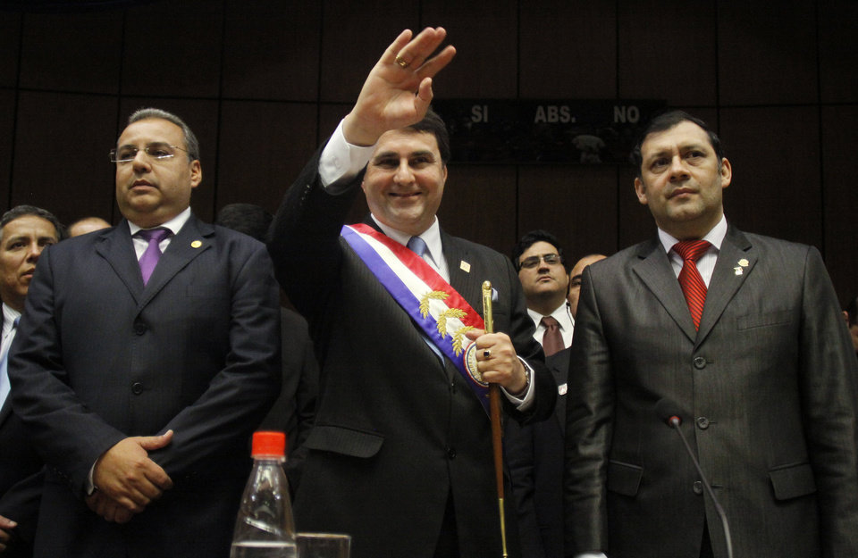 Paraguay's new President Federico Franco waves as he is flanked by Congressional President Jorge Oviedo Matto, left, and lower house President Victor Bogado during his swearing-in ceremony at Congress in Asuncion, Paraguay, Friday, June 22, 2012. Franco was promptly sworn in as president after Paraguay's Senate voted to remove President Fernando Lugo from office in an impeachment trial. (AP Photo/Cesar Olmedo)