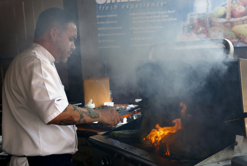 Photo -  Jonas Favela of Boulevard Steakhouse grills during Open Flame at American Propane in Oklahoma City. Photo by Sarah Phipps, The Oklahoman   SARAH PHIPPS -  SARAH PHIPPS