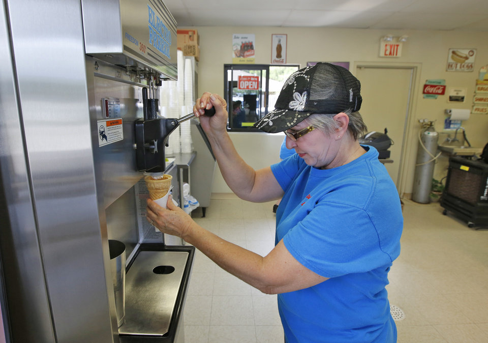 Photo -  Dairy Boy Drive-In owner Karen Bratcher makes a soft-serve ice cream cone for a customer.    Steve Gooch -