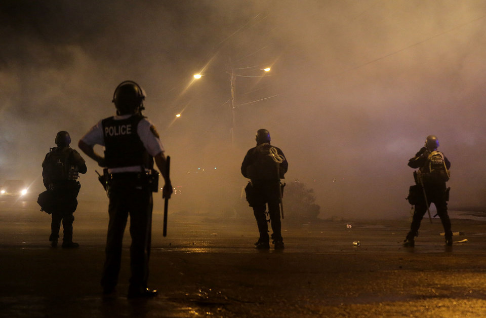 Photo - A law enforcement officer watches Sunday, Aug. 17, 2014, as tear gas is fired to disperse a crowd protesting the shooting of teenager Michael Brown last Saturday in Ferguson, Mo. Brown's shooting in the middle of a street following a suspected robbery of a box of cigars from a nearby market has sparked a week of protests, riots and looting in the St. Louis suburb. (AP Photo/Charlie Riedel)