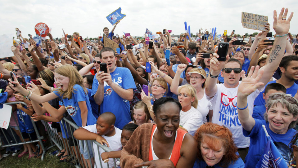 Photo - Thunder fans cheer for the team as the players arrive at a welcome home rally for the Oklahoma City Thunder in a field at Will Rogers World Airport after the team's loss to the Miami Heat in the NBA Finals, Friday, June 22, 2012. Photo by Nate Billings, The Oklahoman