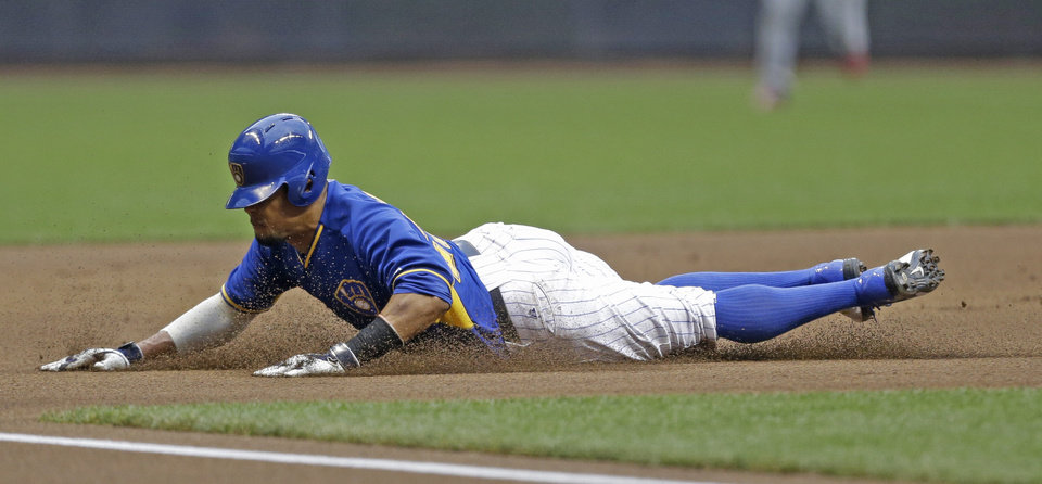 Photo - Milwaukee Brewers' Carlos Gomez steals third base during the first inning of a baseball game against the St. Louis Cardinals Friday, July 11, 2014, in Milwaukee. (AP Photo/Jeffrey Phelps)