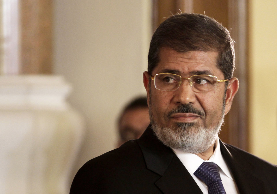 Photo - FILE - In this Friday, July 13, 2012 file photo, Egyptian President Mohammed Morsi holds a joint news conference with Tunisian President Moncef Marzouki, unseen, at the Presidential palace in Cairo, Egypt. The Egyptian army sealed off the presidential palace with barbed wire and armored vehicles Thursday as protesters defied a deadline to vacate the area, pressing forward with demands that Islamist leader Mohammed Morsi rescind decrees giving himself near-absolute power and withdraw a disputed draft constitution.(AP Photo/Maya Alleruzzo, File)