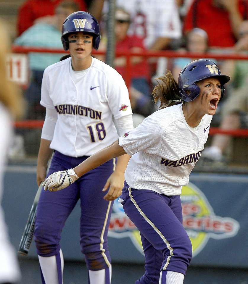 Photo - Washington's Kimi Pohlman, right, reacts after scoring as Morgan Stuart watches in the first inning during the second softball game of the championship series between Washington and Florida in Women's College World Series at ASA Hall of Fame Stadium in Oklahoma City, Tuesday, June 2, 2009. Photo by Bryan Terry, The Oklahoman