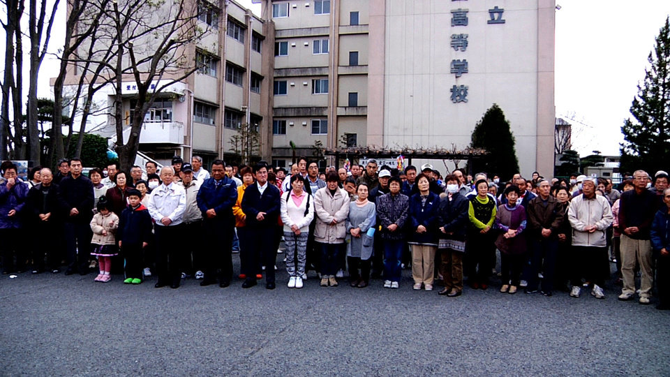 "In this image made from promotional footage for the film ""Nuclear Nation"" released by the 2012 Documentary Japan, Big River Films, Futaba mayor Katsutaka Idogawa, sixth from left in white jacket, poses with evacuees from Futaba town in front of their shelter, the abandoned Kisai high school, in Kazo, Saitama prefecture, near Tokyo, on March 11, 2012, a year after the tsunami and earthquake hit northern Japan. The film ""Nuclear Nation,"" directed by Atsushi Funahashi, documented a story of the residents of Futaba, the town where the tsunami crippled Fukushima Dai-ichi nuclear power plant is located. The March 2011 catastrophe in Japan has set off a flurry of independent films telling the stories of regular people who became overnight victims, stories the creators feel are being ignored by mainstream media and often silenced by the authorities. Nearly two years after the quake and tsunami disaster, the films are an attempt by the creative minds of Japan�s movie industry not only to confront the horrors of the worst nuclear disaster since Chernobyl, but also as a legacy and to empower the victims by telling their story for international audiences. (AP Photo/2012 Documentary Japan, Big River Films) CREDIT MANDATORY, EDITORIAL USE ONLY"