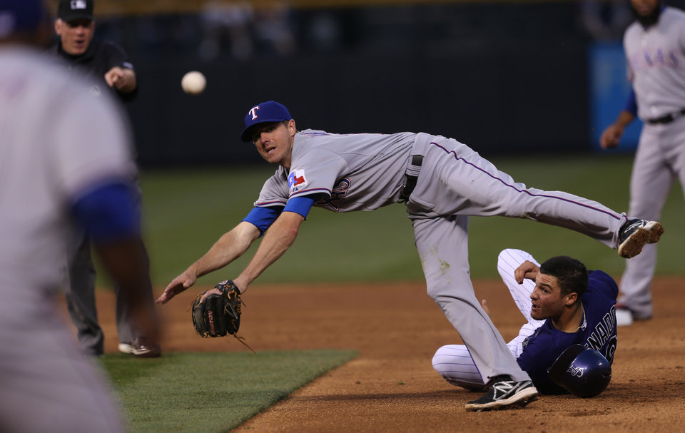 Photo - Texas Rangers second baseman Josh Wilson, back top, flies over Colorado Rockies' Nelson Arenado to throw to first baseman Prince Fielder after tagging out Arenado on the front end of a double play that ended the third inning of an interleague baseball game in Denver on Monday, May 5, 2014. (AP Photo/David Zalubowski)