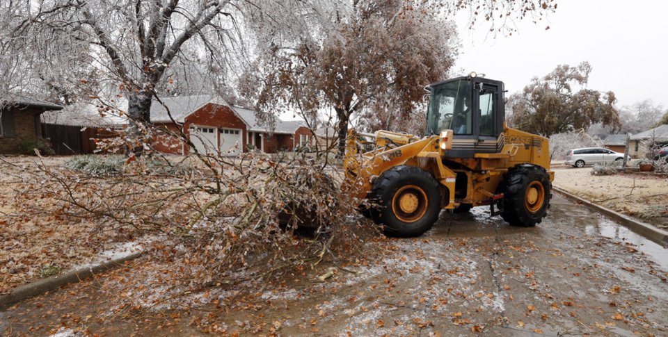 Photo - Jeff Chandler uses a front end loader to move a tree branch off of Pickard Street after a winter storm that coated trees with a thick layer of ice on Saturday, Dec. 21, 2013 in Norman, Okla.  Photo by Steve Sisney, The Oklahoman