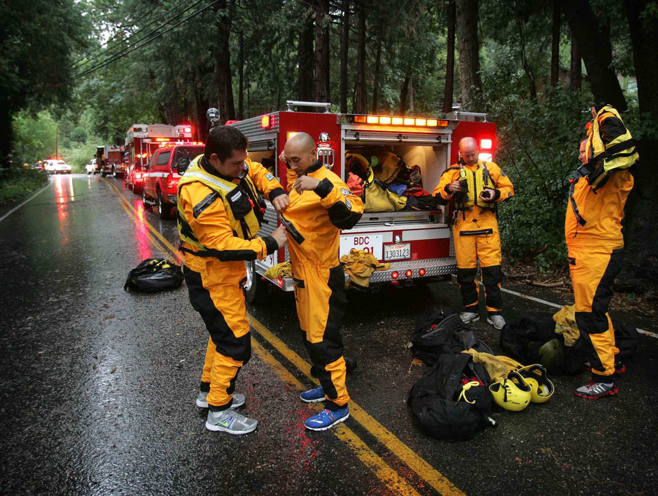 Photo - In this Sunday, Aug. 3, 2014 photo, Swift Water Rescue team members from San Bernardino County Fire Department suit up as they wait for a portion of the road to be cleared, following rock and mudslides in the Forest Falls, Calif. area. Crews on Monday have cleared several feet of mud, rocks and debris that had blocked San Bernardino County roads, stranding some 2,500 people in the rural communities of Oak Glen and Forest Falls. (AP Photo/The Press-Enterprise, David Bauman)  MAGS OUT; MANDATORY CREDIT