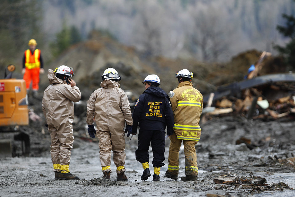 Photo - Rescue workers and work crews  toil at the western edge of the mudslide where it covers Highway 530 Wednesday morning, March 26, 2013, east of Oso, Wash.  Search crews using dogs, bulldozers and their bare hands kept slogging through the mess of broken wood and mud.  (AP Photo/The Herald, Mark Mulligan)  Photo taken 20140326