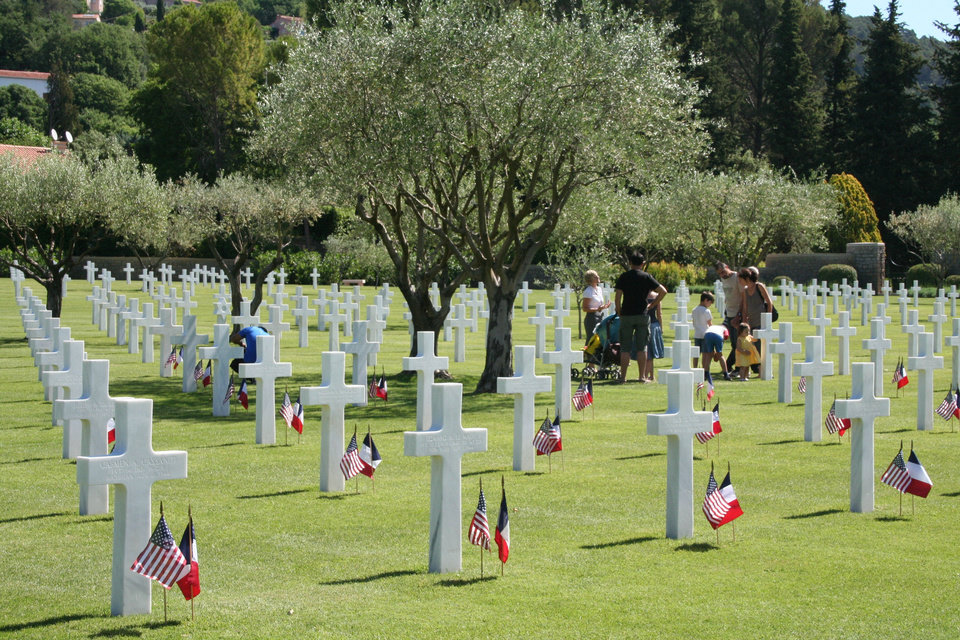 """Photo - Families walk among graves at Rhone American Cemetery in Draguignan, France, which are decorated for Memorial Day with American and French flags. The Oklahoman staff member Don Gammill shares stories from his stepfather, Robert W. """"Bob"""" Hazen, about Hazen's war experiences and two of Hazen's brothers, who were killed in action. Pages 10A-11A. PHOTO PROVIDED BY Franco-American Society/American Battle Monuments Commission"""