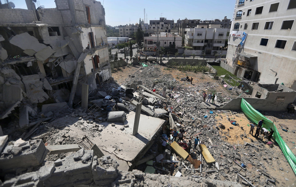 Photo - Palestinians inspect the rubble of a building after it was hit by an Israeli missile strike in Gaza City, Friday, July 11, 2014. Israel launched the Gaza offensive to stop incessant rocket fire that erupted after three Israeli teenagers were kidnapped and killed in the West Bank and a Palestinian teenager was abducted and burned to death in an apparent reprisal attack. The military says it has hit more than 1,100 targets already, mostly what it identified as rocket-launching sites, bombarding the territory on average every five minutes.(AP Photo/Hatem Moussa)