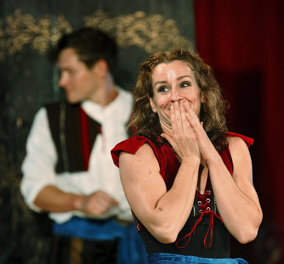 Photo - Blaze Birge faces the audience and covers her mouth in an expression of embarrassment after she missed the target with her last two knives during a knife-throwing act featuring Birge and her husband, David Jones, background, who is looking behind him to see where the knives landed. Performers in the Zoppe Italian Family Circus entertain a crowd of about 500 fairgoers under the big top tent in the Centennial Plaza at the Oklahoma State Fair on Wednesday,  Sep. 18, 2013. Photo  by Jim Beckel, The Oklahoman.