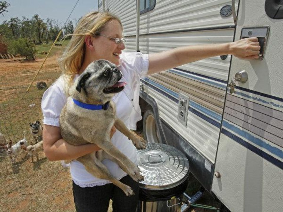Kara Stanley moves Trey, one of the residents of the Pug Sanctuary, back into her temporary home on Thursday, June 9, 2011, in Dibble, Okla.  Pug Sanctuary Inc.'s facility was heavily damaged in May 24 and Stanley wants to rebuild. Photo by Steve Sisney, The Oklahoman ORG XMIT: KOD